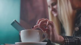 Using gadgets. Mobile tablet in the hands of women. Cute with a tablet sitting at the table in cafe. Stylish girl in a plaid shirt is interested enjoys the stock footage