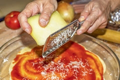 Using a grater to grate cheese Stock Images