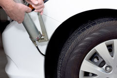 Using a grease gun to lubricate a car Royalty Free Stock Photography