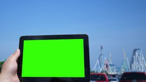 Using a green screen tablet by an amusement park. July 4 2018 stock footage