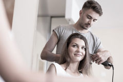Using hair straightener. Hairdresser using hair straightener at hair salon Royalty Free Stock Photography