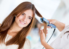 Using a hair straightener at the salon Stock Photo