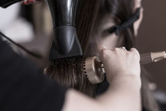 Using hairbrush and hair dryer Stock Image