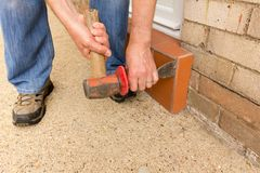 Using a hammer and Bolster. Man using a hammer and bolster to remove tiles from a door step stock images