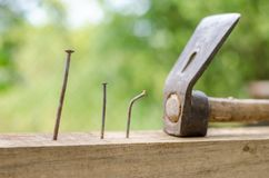 Using hammer and nails and curved nail on wood and bokeh background.  Stock Image