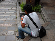 Using a handyphone. Boy using a handiphone in a traditional street Royalty Free Stock Photo
