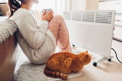 Using heater at home in winter. Woman warming and drinking tea with cat. Heating season stock image