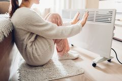 Using heater at home in winter. Woman warming her hands. Heating season. Using heater at home in winter. Woman warming her hands sitting by device and wearing stock photos