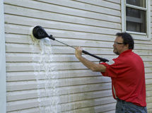 Using A High Pressure Brush To Clean Algae And Mold Off Vinyl Si Stock Image