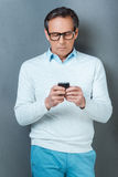 Using his phone for being in touch. Royalty Free Stock Image
