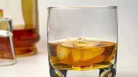 Using ice tongs drop ice cubes into glass filled with whiskey.