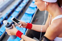Using iphone. Modern girl in activewear using iphone at stadium stock photo