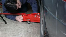 Placing a red jack under a gray car. Using jack to prep for changing a tire stock video footage