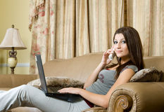 Using laptop. Women sitting in the couch using laptop Stock Images