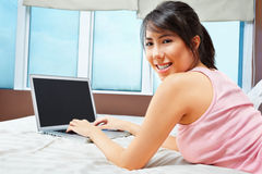 Using laptop on bed Royalty Free Stock Photography