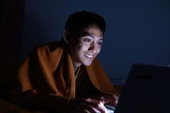Using laptop on bed at night. Using laptop in the middle at the night stock image