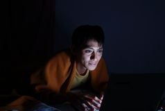Using laptop on bed at night Stock Photos