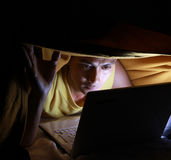 Using laptop in the blanket. Using laptop in the middle at the night royalty free stock photography