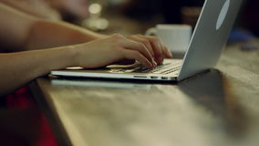 Using laptop in a cafe. Close up view of man hands typing on a laptop in a cafe, cup of coffee on background stock footage