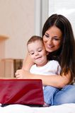 Using laptop at home. Mother and son are using laptop at home Stock Photos