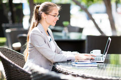 Using laptop in outdoor cafe Royalty Free Stock Image