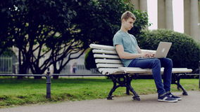 Using laptop in a street. Young happy man using laptop sitting on a bench in a street stock video