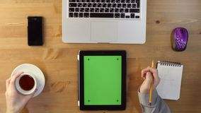 Using Laptop and Tablet PC with a Green Screen. At the Desktop.Top View stock footage