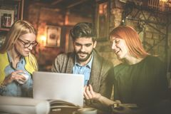 Using laptop together. Students people. Three young student using laptop together and having funny conversation Royalty Free Stock Image