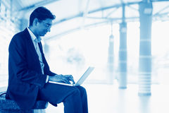 Using laptop at train station Royalty Free Stock Photography