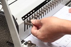 Using the left hand adorned gear to penetrate the paper. Preparation for Binding. Binding documents ,Using the left hand adorned gear to penetrate the paper royalty free stock photos