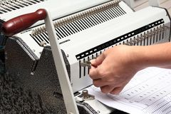 Using the left hand adorned gear to penetrate the paper. Preparation for Binding. Binding documents ,Using the left hand adorned gear to penetrate the paper stock photography