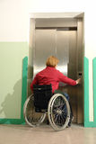 Using lift. Handicapped woman on wheelchair using lift in building Stock Image