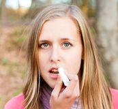 Using lip balm. Young beautiful woman using lip balm to prevent dehydration during winter royalty free stock photos