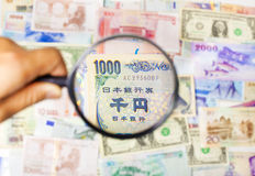 Using a magnifier to search the method of Asian Market Stock Photos