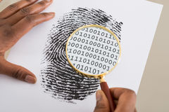 Using Magnifying Glass To Check Binary Code Within Finger Print. Close-up Of Person Using Magnifying Glass To Check Binary Code Within Finger Print Royalty Free Stock Photo