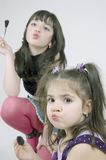 Using make-up. Two little girls with make up on their faces stock photography