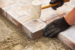 Using a mallet to set paver. Installing paver bricks on patio, mallet to level the stones Royalty Free Stock Photos