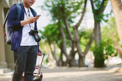 Using map in smartphone. Cropped image of tourist using map in smartphone when standing outdoors Royalty Free Stock Photos