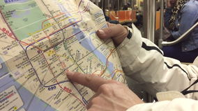 Using map in the subway in NYC. Tourists using map in the subway in NYC stock video