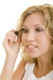 Using mascara. Blonde woman is using mascara stock image