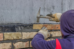 Using mason hammer to tap brick into position Royalty Free Stock Image