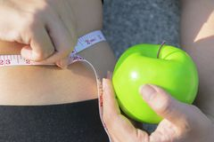 She is using the measuring tape. And holding green apples stock image