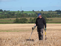 Using a metal detector in field. Metal detecting in a field of stubble royalty free stock image