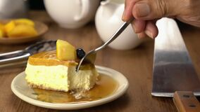 Using metal spoon eating delicious homemade mango cheesecake with honey in a ceramic dish on wooden table.