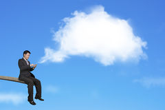Using mobile businessman on springboard with white thought bubbl. Using mobile phone businessman sitting on springboard with white cloud thought bubble and blue Royalty Free Stock Photos