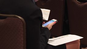 Using a mobile device at a meeting (4 of 5). A woman uses her smart phone during a business conference stock footage