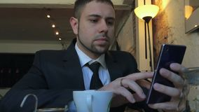 Using mobile phone on business lunch. Close up of young bearded businessman in black suit using mobile phone while sitting at the cafe with a cup of coffee or stock video footage