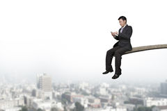 Using mobile phone businessman sitting on springboard with citys Royalty Free Stock Photo