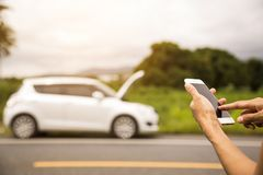 Using a mobile phone call a car mechanic because car was broken. Royalty Free Stock Photography