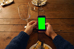 Using mobile phone in restaurant Royalty Free Stock Photography